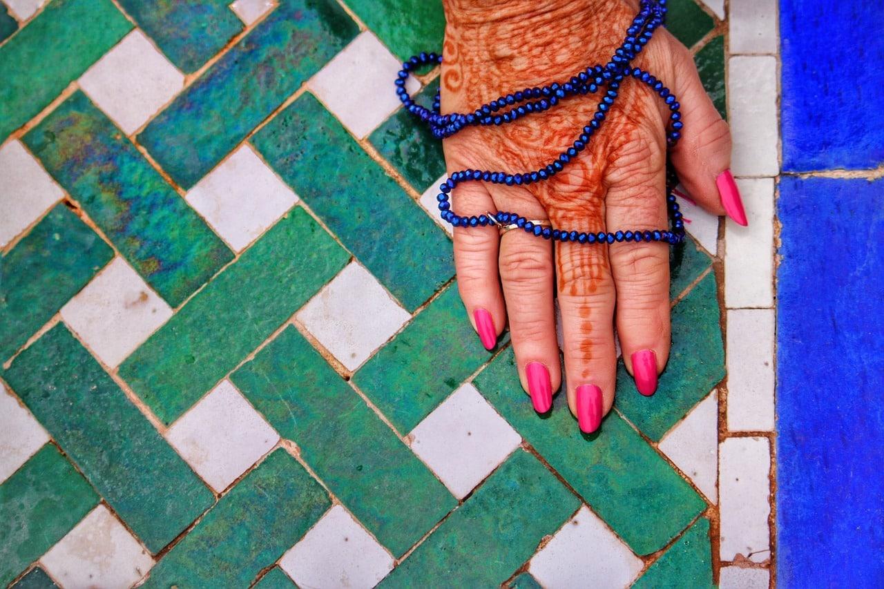 hand met henna en mala op gekleurde tegels